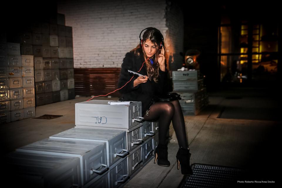 Una ragazza ascaolta in cuffia l'installazioen di arte contemporanea in Area Docks a Brescia